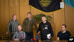 Slovyansk belediye başkanı Vaçislav Ponomarev(sağdan ikinci) basın toplantısında rehin alınan yabancı askeri gözlemcilerle