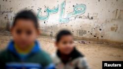 ເດັກນ້ອຍປາແລສໄຕນ໌ ພາກັນຢືນຢູ່ຕໍ່ໜ້າຝາ ທີ່ຖືກທຳລາຍ ຈາກສົງຄາມ ໃນປີ 2014 ທີ່ Beit Hanoun ພາກເໜືອຂອງ ເຂດ Gaza.