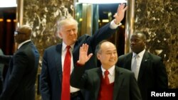 Presiden AS terpilih Donald Trump dan CEO Softbank Masayoshi Son melambaikan tangan pada para tamu setelah melakukan pembicaraan di Trump Tower di Manhattan, kota New York (6/12). (Reuters/Brendan McDermid)