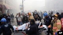 Nhân viên cứu hộ khiêng một người bị thương trên cáng ra khỏi tòa nhà bị sụp đổ ở Harlem, New York, ngày 12/3/2014.
