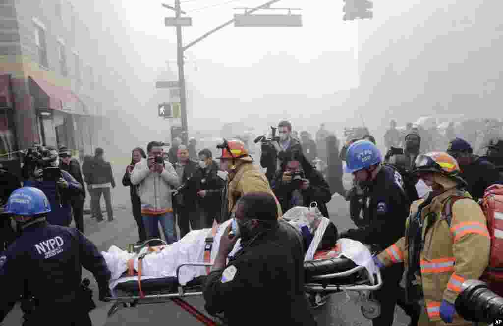 Equipas de socorro retiram um ferido dos escombros após a explosão de um prédio em Harlem, Nova Iorque, Março 12, 2014.