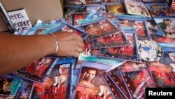 FILE - A policeman looks at pirated Digital Video Disks (DVD) of a fight between Manny 'Pacman' Pacquiao of Philippines and Ricky Hatton of Britain during a raid in Manila.