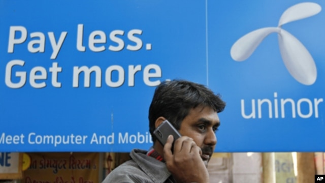 A man speaks on a mobile phone in front of a billboard of Uninor at a market in Ahmedabad, February 6, 2012.  Telenor's joint venture with Unitech, which operates under the Uninor brand, has been among the most aggressive of India's newer telecoms compani