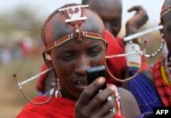 FILE - A Maasai moran uses a mobile phone in the village of Mbirukani in Kajiado, June 27, 2015.