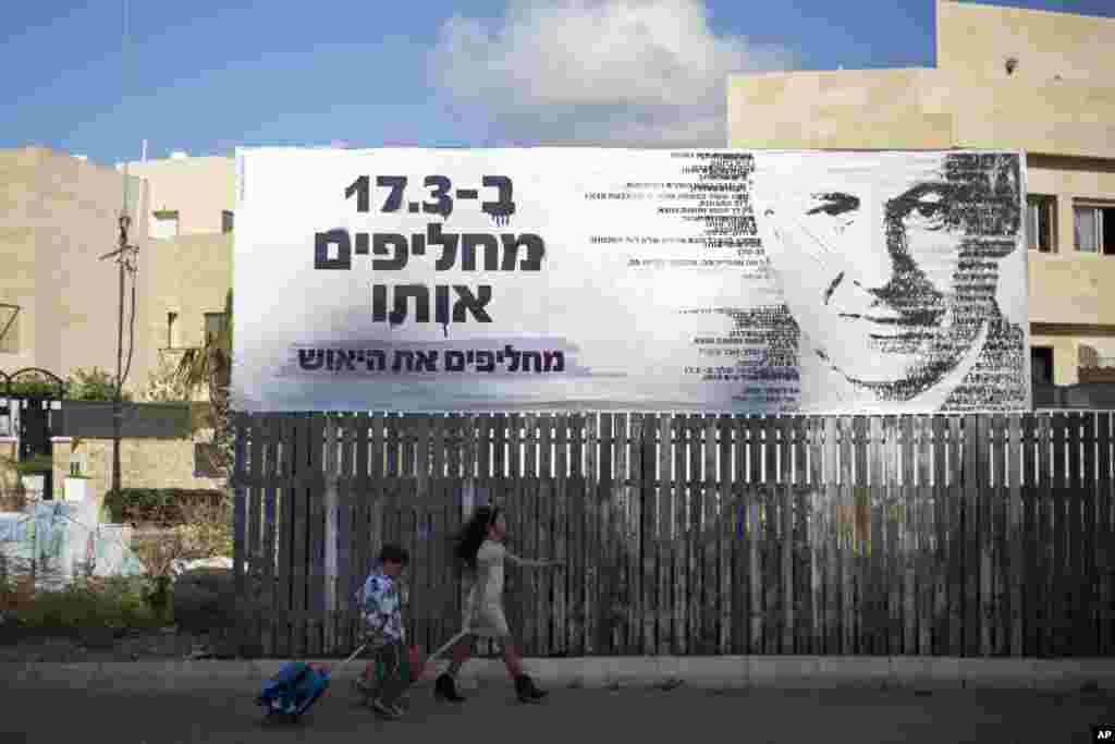 Israel will hold a general election on March 17 and Prime Minister Benjamin Netanyahu seeks to secure his fourth term as prime minister. In this photo, children pass by an election campaign banner with an image of Israel's Prime Minister Benjamin Netanyahu, in Netanya, Israel, March 2, 2015.