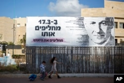 Children pass a campaign poster for Israeli Prime Minister Benjamin Netanyahu, who seeks a fourth term. The Hebrew poster says of the general election: 'On March 17, we replace him, we replace the despair.'