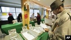 """Petugas kantor pos di Chicago, AS, membaca dan memilah-milah surat yang dikirim untuk program """"Surat untuk Sinterklas"""". (AP/M. Spencer Green)"""