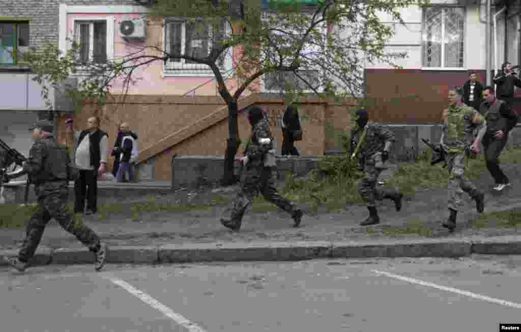 Pro-Russian armed men run near the local police headquarters in Luhansk, eastern Ukraine.