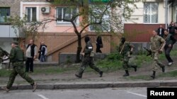 Dân quân vũ trang thân Nga chạy ngang trụ sở cảnh sát địa phương ở Luhansk, miền đông Ukraine, ngày 29/4/2014.