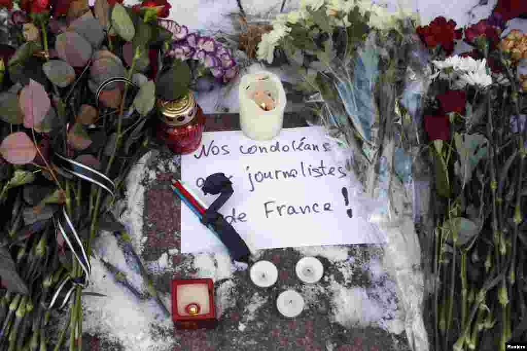 Candles, condolence flowers and pencils for the victims of the shooting at Charlie Hebdo are placed outside the French embassy in Kiev, Jan. 8, 2015.