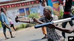 Un manifestant utilise un lance-pierre au cours des affrontements avec les forces de sécurité dans le quartier de Cibitoke de la capitale Bujumbura, Burundi vendredi 29 mai 2015.
