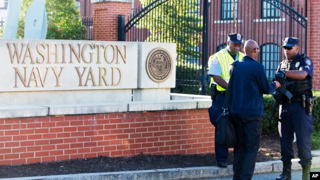 An officer (R) checks an ID outside of the Washington Navy Yard in the U.S. capital on September 17, 2013.
