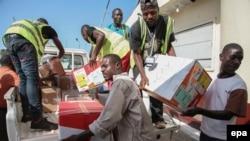 Des travailleurs déchargent un avion à l'aéroport Spriggs Payne à Monrovia, au Libéria, 2 avril 2014. epa/ AHMED JALLANZO