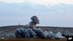 FILE - Smoke rises above the Syrian city of Kobani after an airstrike by the U.S.-led coalition, seen from a hilltop on the outskirts of Suruc, near the Turkish border.