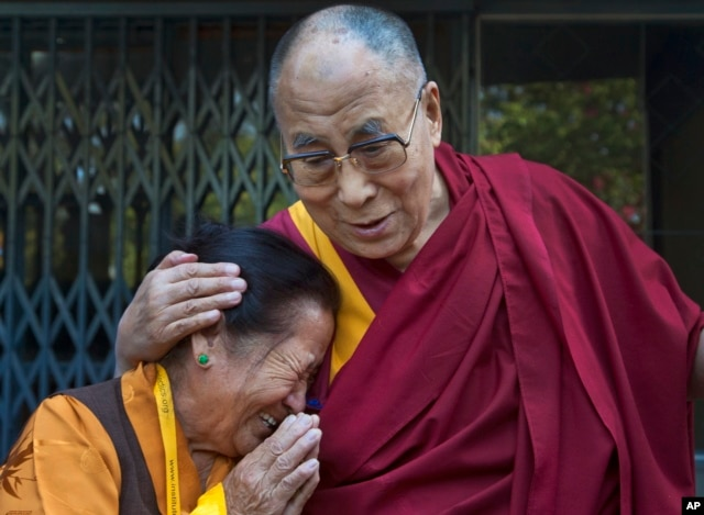 FILE - An elderly Tibetan woman, who was among those waiting to receive the Dalai Lama, gets emotional as the spiritual leader greets devotees upon arrival at the Institute of Buddhist Dialectics near Dharmsala, India.