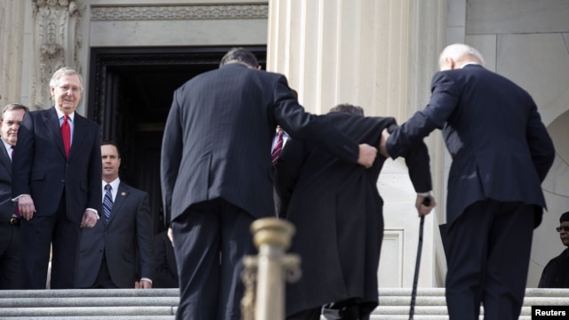U.S. Senate Minority Leader Mitch McConnell (L) watches as Senator Mark Kirk (2nd R) works his way up the Senate steps with the assistance of Senator Joe Manchin (2nd L) and U.S. Vice President Joseph Biden on his return to the U.S. Senate on Capitol Hill, Washington, January 3, 2013.