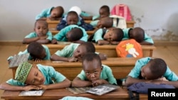 FILE - Boys rest their heads on their desks during a language class in Cameroon's capital, Yaounde. Strikes by teachers and lawyers to push for more use of English have turned violent, and schools have closed.