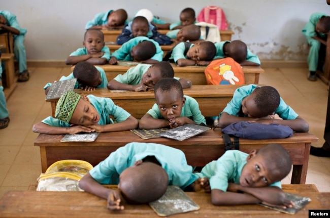 FILE - Muslim boys rest their heads on their desks during a language class at Al-Haramain madrassa at the Islamic Complex in Cameroon's capital Yaounde.