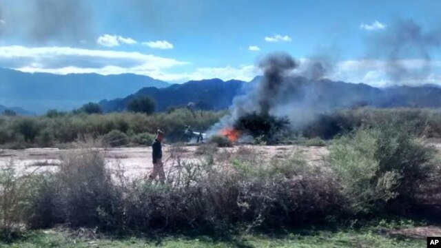 A man stands near the smoking remains of a helicopter that crashed with another near Villa Castelli in the La Rioja province of Argentina, Monday, March 9, 2015.