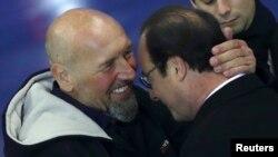 Le président français François Hollande (gauche) et l'ex-otage Serge Lazarevic s'étreignent après avoir prononcé des discours à l'aéroport militaire de Villacoublay, près de Paris, le 10 décembre 2014.