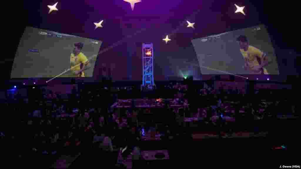 Proyektor-proyektor memancarkan pertandingan-pertandingan ke layar di sisi-sisi stadion.