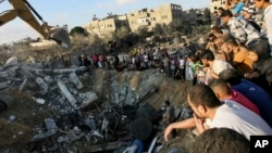 غزہ کے شہری اس عمارت کے ملبے کے پاس کھڑے ہیں جہاں ہفتے کو اسرائیل کی بمباری سے ایک ہی خاندان کے 20 افراد ہلاک ہوئے