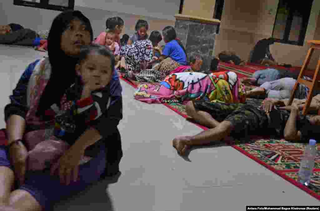 Residents sit inside a mosque where they evacuated following high waves and the eruption of the Krakatoa volcano at Labuan district in Pandeglang regency, Banten province, Indonesia, Dec. 22, 2018.
