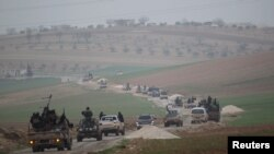 FILE - Members of al-Qaida's Nusra Front drive in a convoy as they tour villages in the southern countryside of Idlib, Syria.