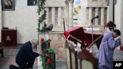 A Christian man and a cleric pray during a New Year mass at Saint Serkis church in central Tehran. New Year is celebrated by the Assyrian and Armenian minorities in Iran, where a majority of its citizens are Muslim, 01 Jan 2011