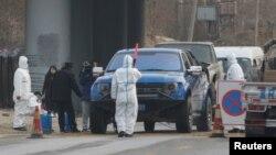 北京房山地区发现非洲猪瘟后,身穿防护服的防疫人员在通往出现疫情的村庄道路上设卡。(2018年11月23日)