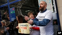 """The owners of a lottery office celebrate after selling the top Christmas lottery prize """"El Gordo"""" or 'The Fat One' in Madrid, Dec. 22, 2017."""