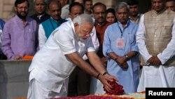 O primeiro-ministro recém eleito, Narendra Modi, deposita pétalas de rosa no memorial de Mahatma Gandhi em Rajghat, após a cerimónia de juramento de posse em Nova Deli, Índia, Maio 26, 2014.
