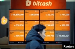 FILE - A man walks past an electric board showing exchange rates of various cryptocurrencies, including Bitcoin, at a cryptocurrencies exchange in Seoul, South Korea, Dec. 13, 2017.