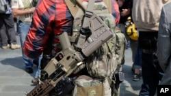 Seorang pria yang berdiri bersama para anggota Patriot Prayer dan kelompok-kelompok lain yang mendukung hak kepemilikan senjata tampak menyandang senjata saat pawai akbar, Sabtu, 18 Agustus 2018, di Balai Kota di Seattle (foto: AP Photo/Ted S. Warren)