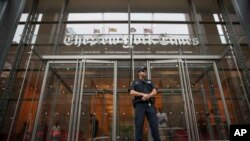 FILE- In this June 28, 2018, file photo, a police officer stands guard outside The New York Times building in New York. Shares of newspaper publisher The New York Times Co. slid Wednesday, Aug. 7, 2019, after the company said a key profit measure slipped, revenue missed Wall Stre