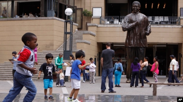 Children play beneath a giant statue of former South African President Nelson Mandela, center back, on Nelson Mandela Square in Sandton, Johannesburg, Sunday, Mar. 10, 2013.