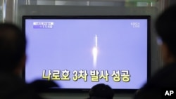 Warga Korea Selatan mengamati televisi di sebuah stasiun kereta di Seoul, Korea Selatan yang menayangkan peluncuran roket pertama Korea Selatan (30/1).