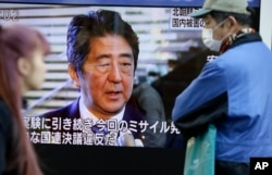 FILE - Passers-by look at a TV screen showing Japanese Prime Minister Shinzo Abe. Many feel Abe's 'Abenomics' policies have not done enough for the economy.