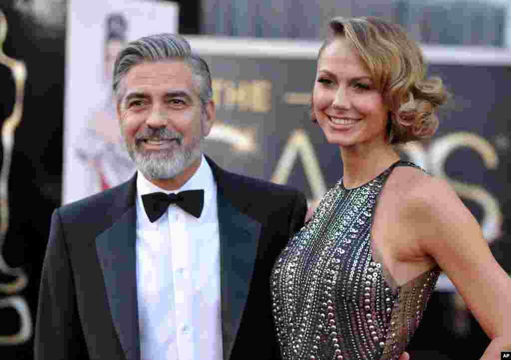 24일 아카데미 시상식을 위해 미국 로스앤젤레스 할리우드 돌비 씨어터에 도착한 배우 조지 클루니(왼쪽)와 18살 연하의 연인 스테이시 키블러.