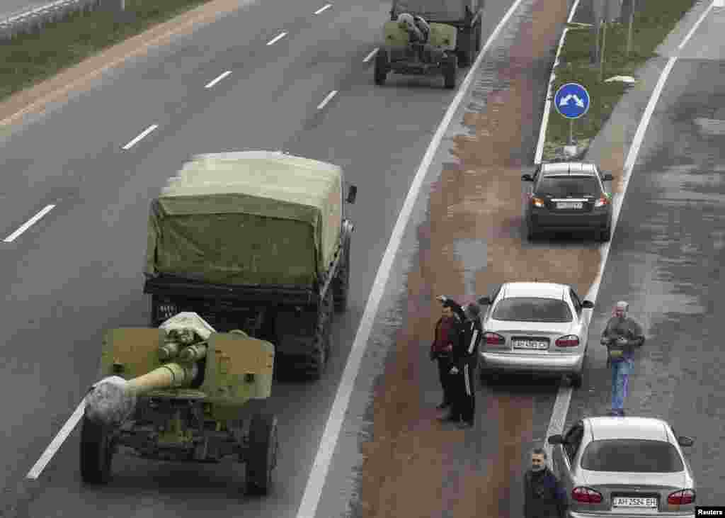 Motorists watch a Ukrainian military convoy pass by near the city of Donetsk, Ukraine, April 10, 2014.