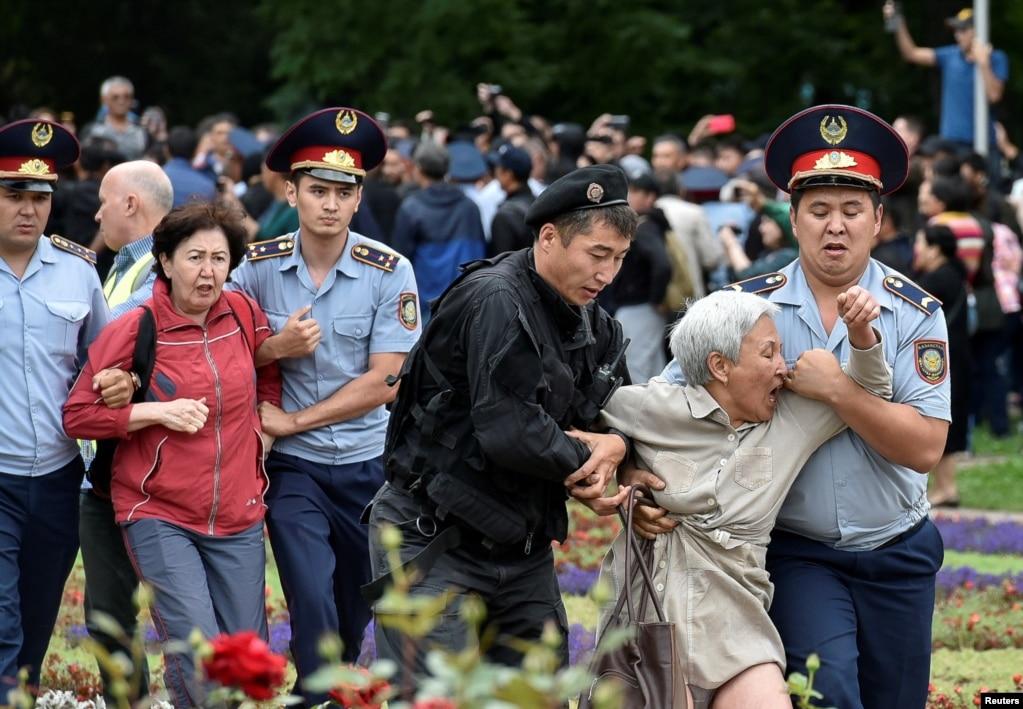 Сотрудники полиции задерживают сторонников оппозиции во время акции протеста против президентских выборов в Алматы, Казахстан.