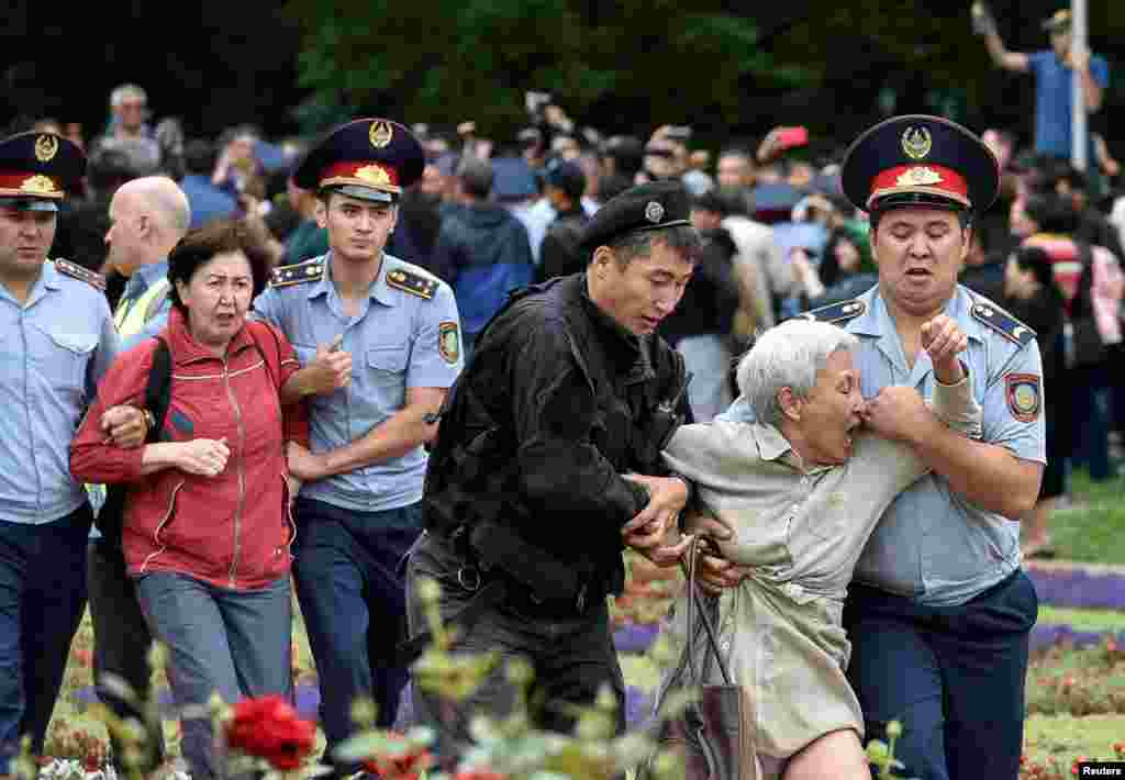 Police officers detain opposition supporters during a protest against the presidential election, in Almaty, Kazakhstan.