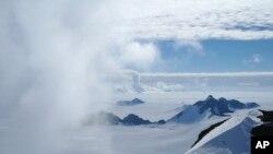 En esta foto de 2011 provista por el investigador Hamish Pritchard, nubes de verano se agitan en torno de los Picos Staccato de la isla Alexander frente a la península antártica.Según un estudio difundido el miércoles 13 de junio de 2018, el derretimiento de la Antártida se acelera a un paso alarmante.