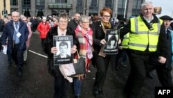 Family members of victims of the 'Bloody Sunday' killings walk in procession holding portraits of their killed relatives in Londonderry on March 14, 2019 following the announcement that a former British soldier will be charged with murder over the 1972 killings.
