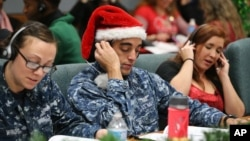Santa tracker volunteers U.S. Navy Petty Officer Brandon Wright, center, and his wife, Petty Officer Emily Wright, left, take phone calls from children asking where Santa is and when he will deliver presents to their homes, inside a phone-in center during
