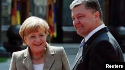 德國總理默克爾,8月23日訪問烏克蘭,和總統波羅申科(右)會晤。
