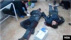 Seorang dokter (kiri) merawat dua orang warga di Baba Amr, provinsi Homs, yang terluka akibat tembakan pasukan Suriah (26/12).
