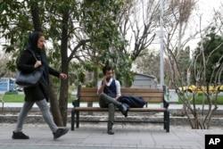 Amir Ali Najafi, a transgender man, talks on his cellphone as a woman walks on a sidewalk in downtown Tehran, Iran, March 11, 2018.
