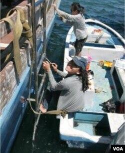 Para mahasiswa sedang mengerjakan lukisan cat pada badan Kapal Gurano Bintang di atas kapal sekoci.