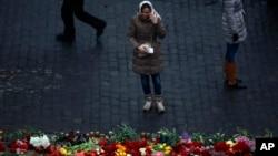 一位烏克蘭婦女在基輔街頭的紀念在抗議衝突中死亡抗議者的花圈前哭泣